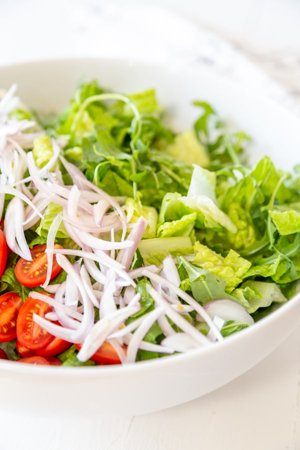 A white bowl with chopped lettuce, sliced tomatoes, and slivered red onion.