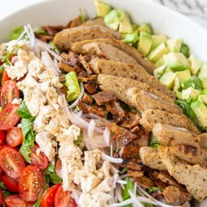 A white bowl with a Cobb salad in it.