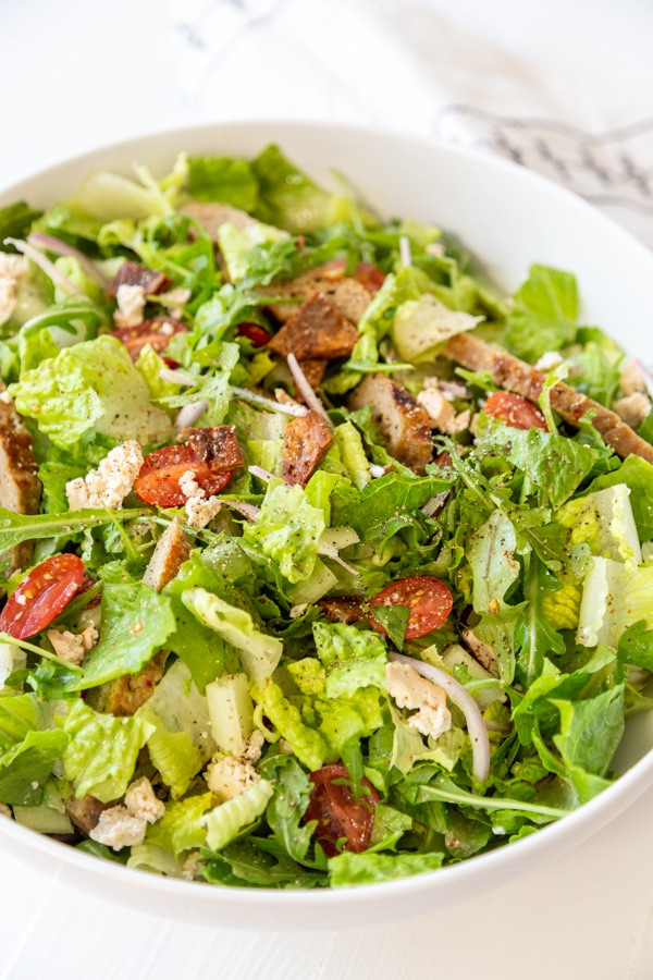 A tossed Cobb salad in a large white bowl.