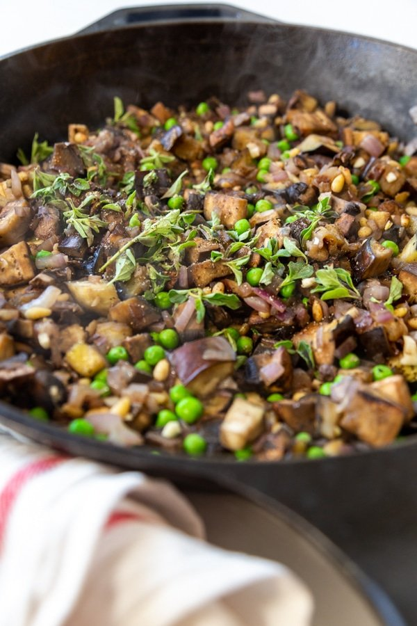 An iron skillet with eggplant, peas, onions, and pine nuts.
