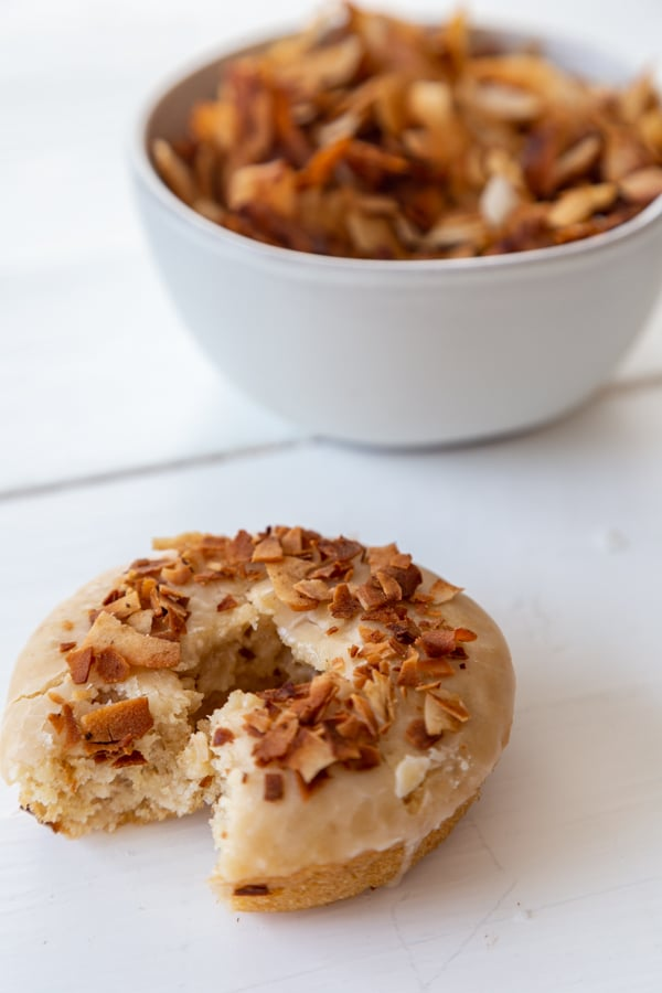 A glazed doughnut with coconut bacon on top with a bite out of it and a white bowl of coconut bacon behind it.