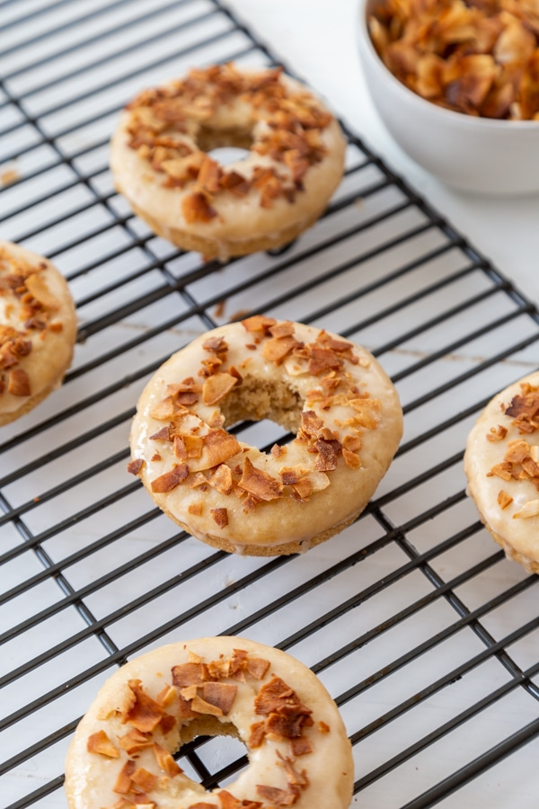 Coconut bacon and maple glazed doughnuts on a cooling rack with a bowl of coconut bacon next to the rack.