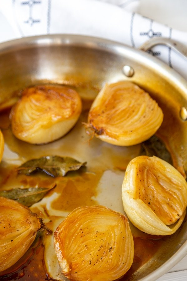A round pan with caramelized baked onions in broth with bay leaves.