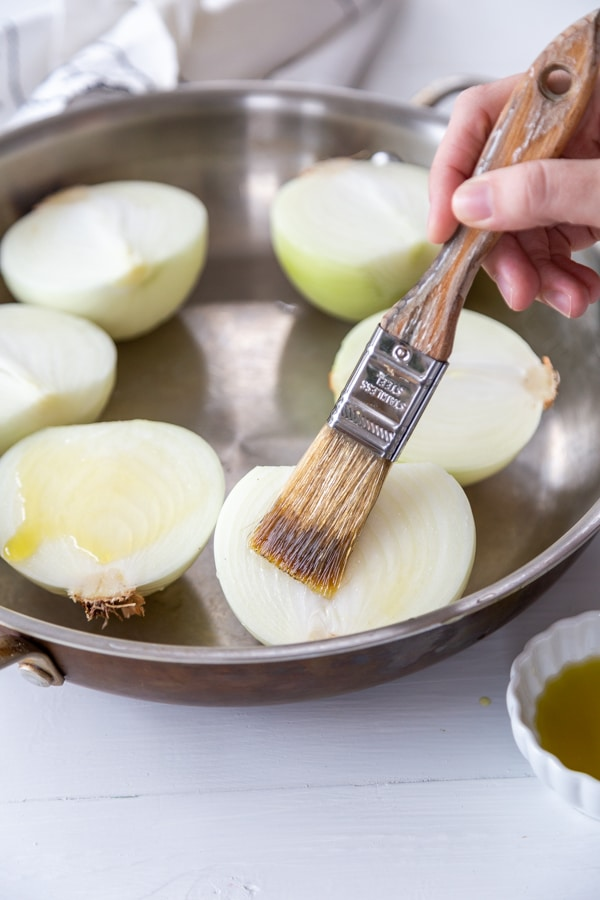 A hand brushing olive oil on halved onions.