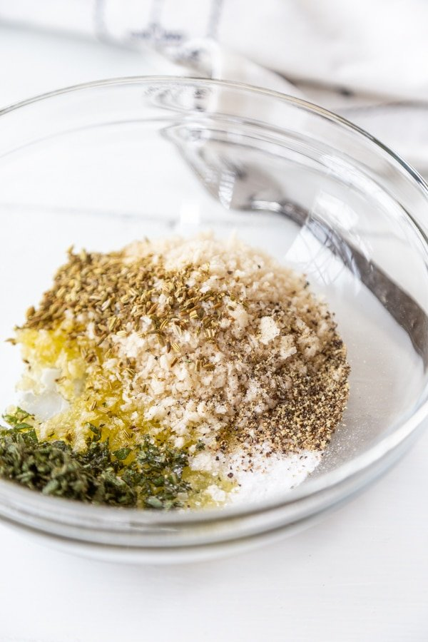 A clear glass bowl with breadcrumbs and spices.