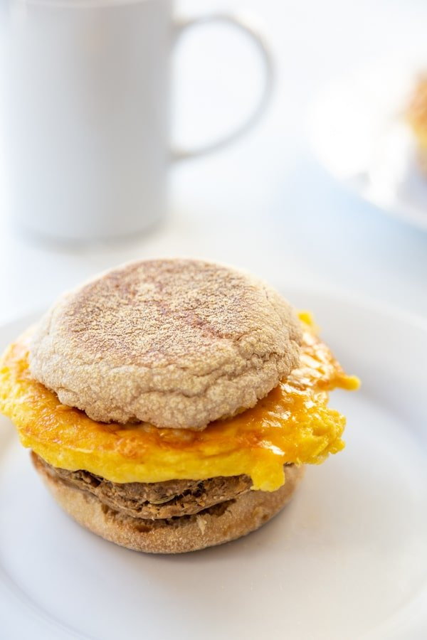 A sausage, egg, and cheese breakfast sandwich on a white plate with a white coffee cup in the background.