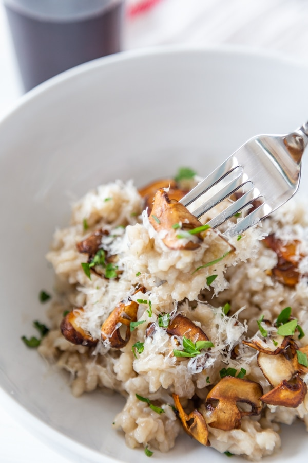 A fork full of mushroom risotto and parmesan cheese over a white bowl of the risotto.