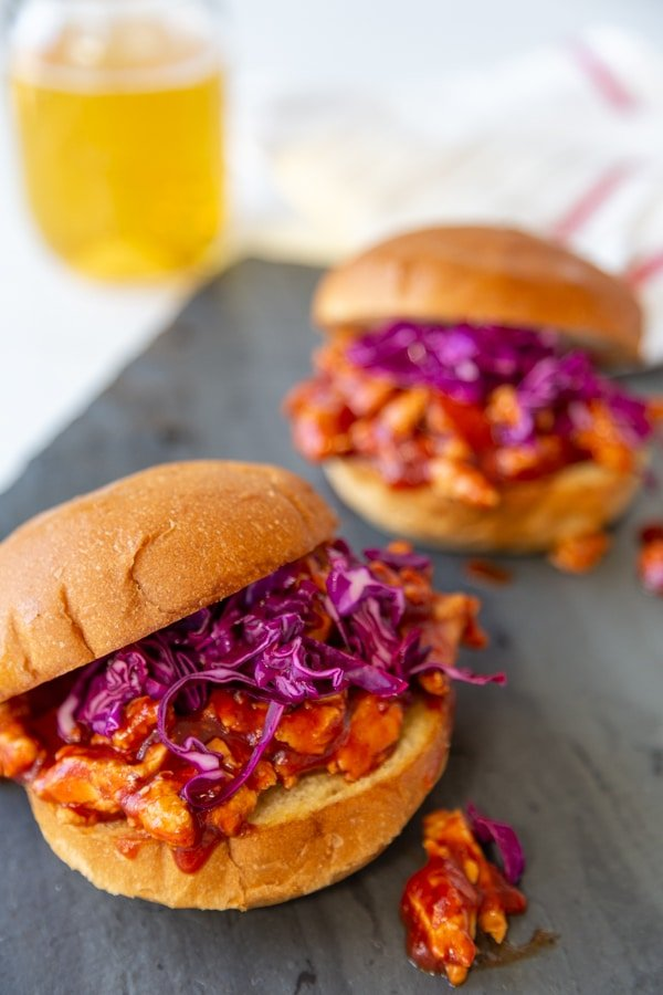 2 pulled BBQ sandwiches with purple slaw on a slate board with a glass of beer in the background.