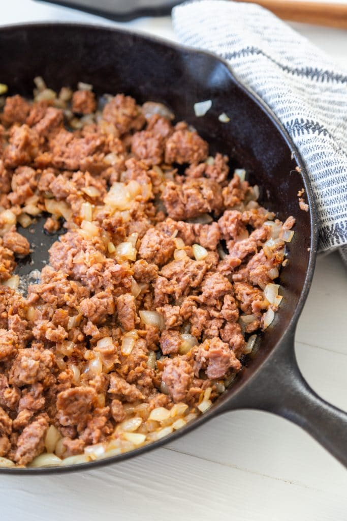 An iron skillet with ground beef.