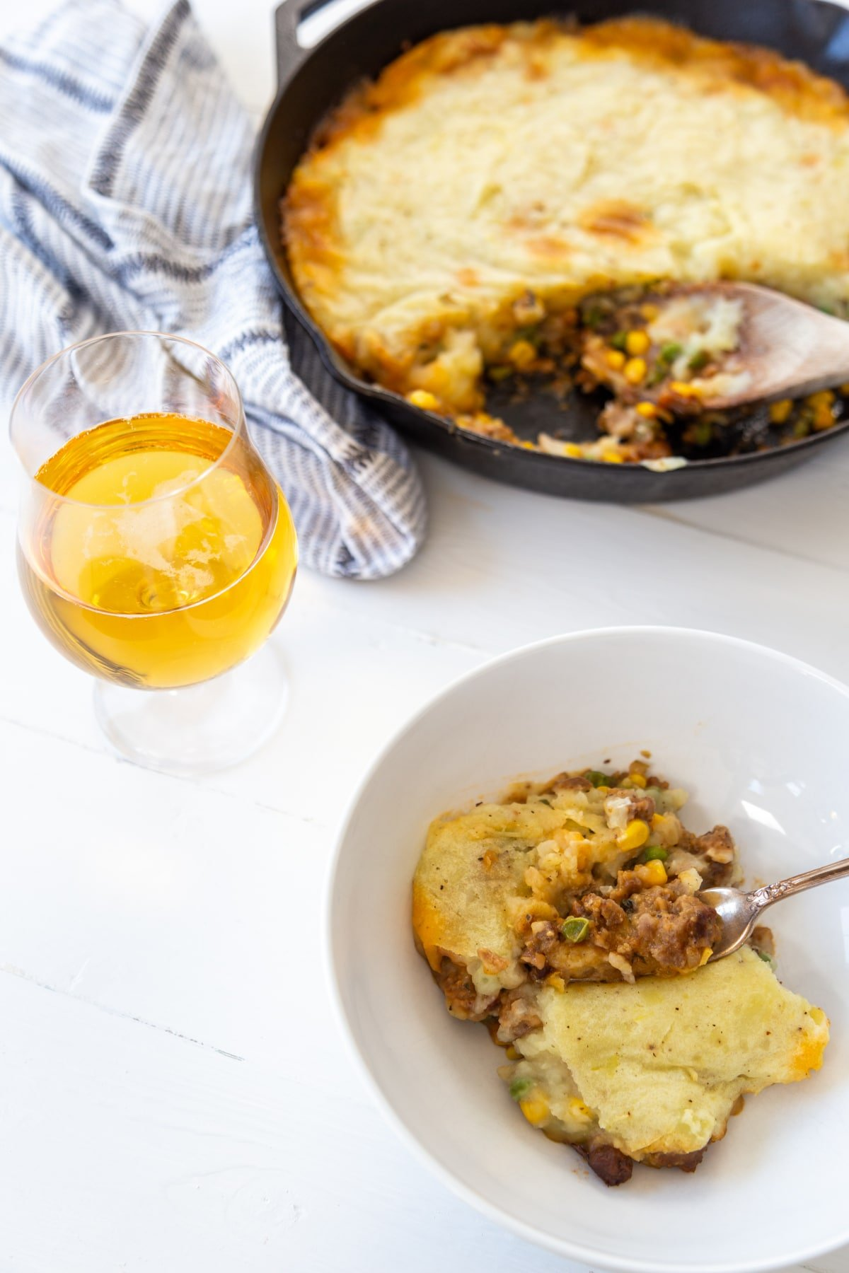 A white bowl of sheperd's pie with a fork and an iron skillet with the pie and a glass of beer in the background.