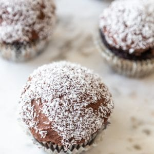 A marble board with 4 chocolate frosted cupcakes with shredded coconut on the tops.