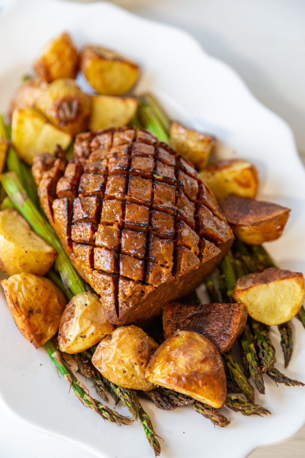 An overhead shot of a seitan ham that's scored on the top with roasted potatoes and a bed of roasted asparagus.