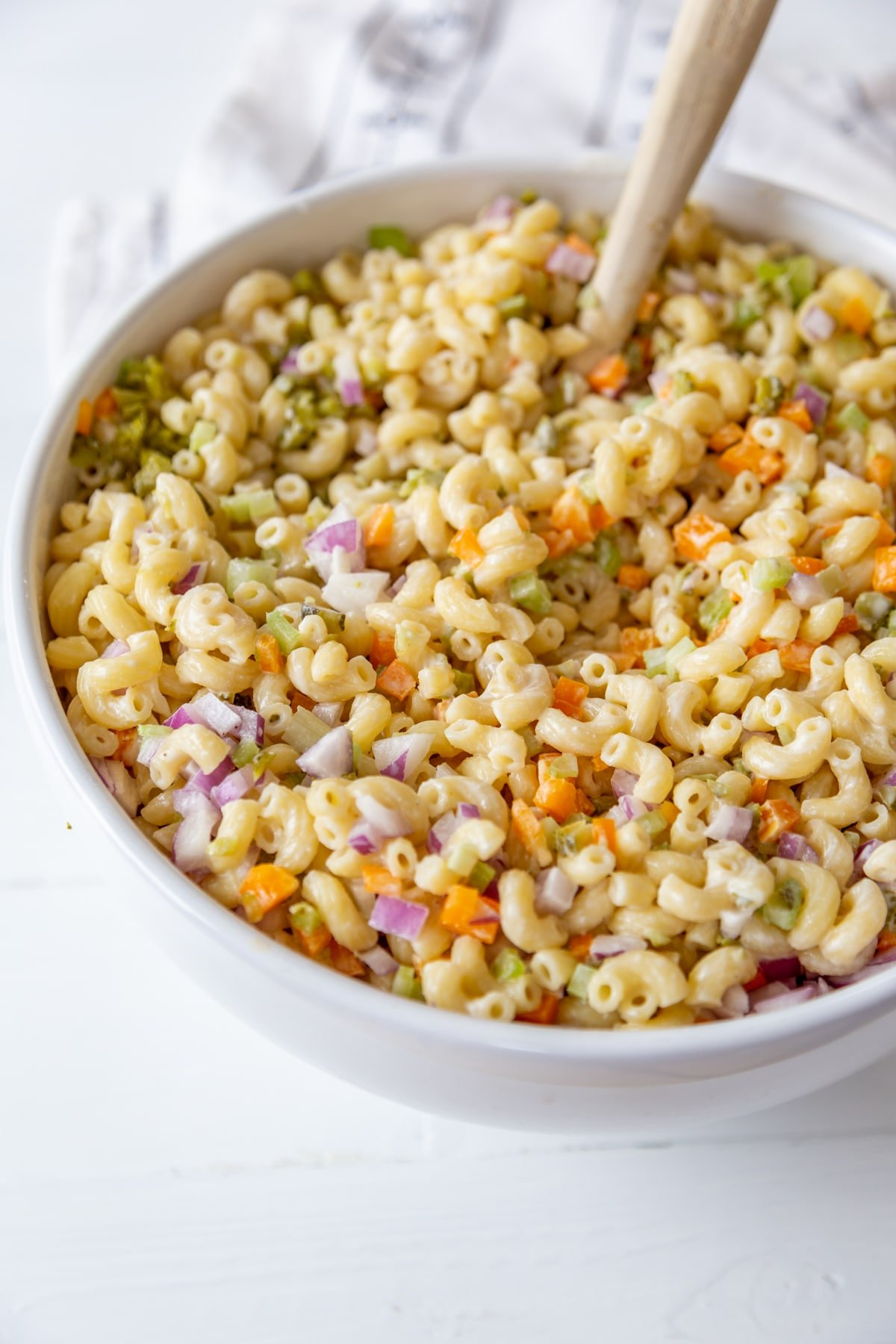 A large white bowl with a wooden spoon stirring macaroni salad.
