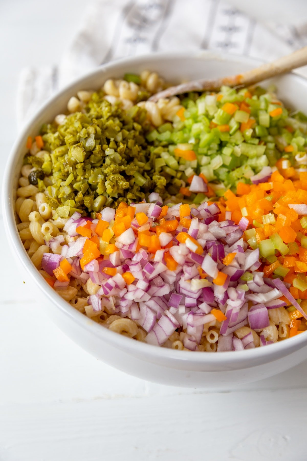 A large white bowl with macaroni, dressing, and chopped vegetables.