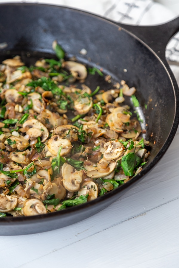 An iron skillet with mushrooms and onions.