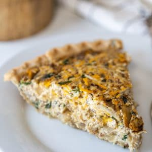 A slice of vegetable and cheese quiche on a white plate with a wooden cake stand and white and black towel behind the plate.