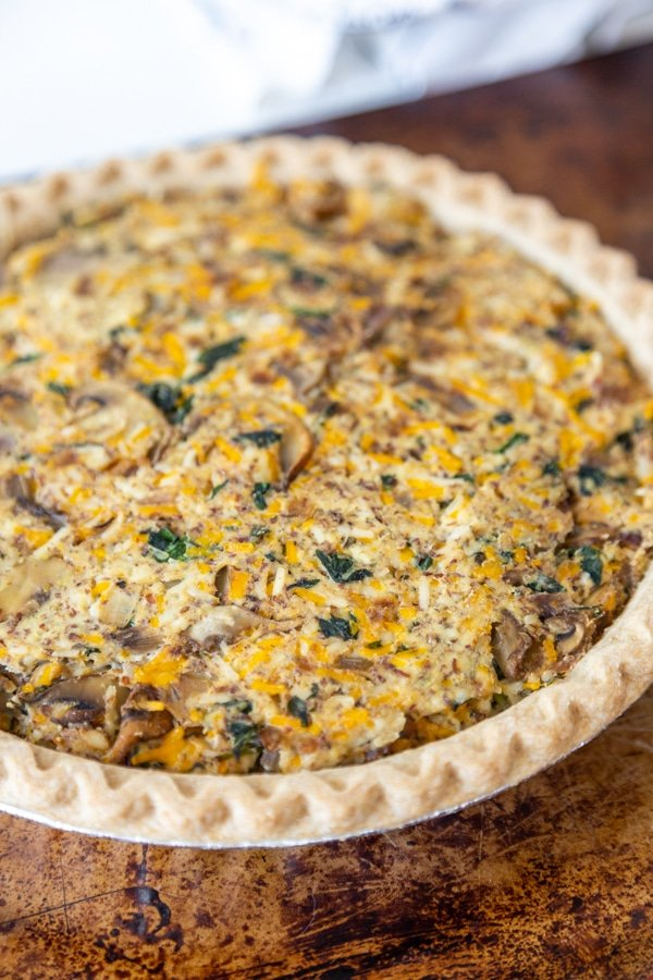 A mushroom and spinach quiche in a pie plate on a metal tray.