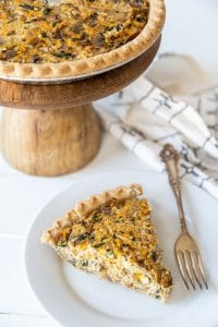 A slice of vegetable quiche on a white plate with a silver fork and a wooden cake stand with the entire quiche behind it.
