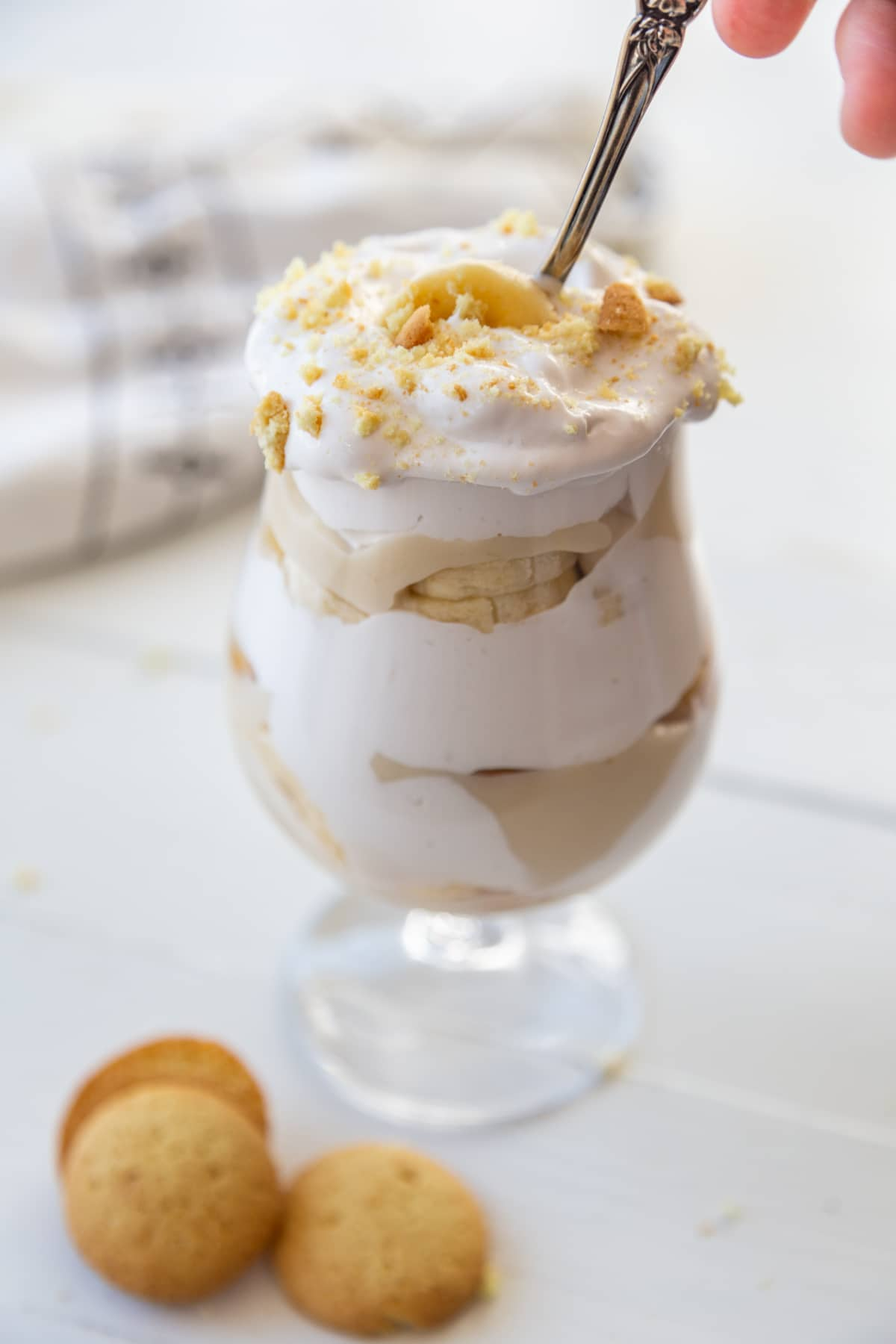 A hand inserting a silver spoon into a glass of banana pudding with 3 vanilla wafers next to the glass.