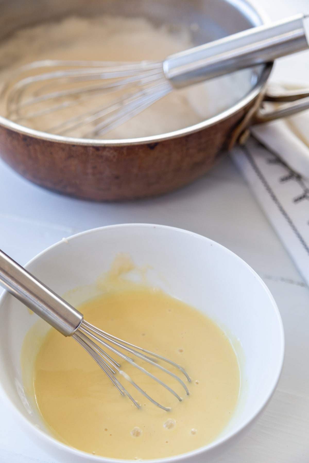 A white bowl with egg and a whisk and a copper pot with vanilla pudding in the background.