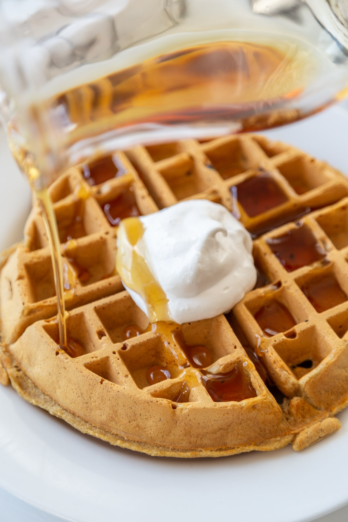 A Belgian waffle with maple syrup being poured over the waffle and whipped topping on a white plate.