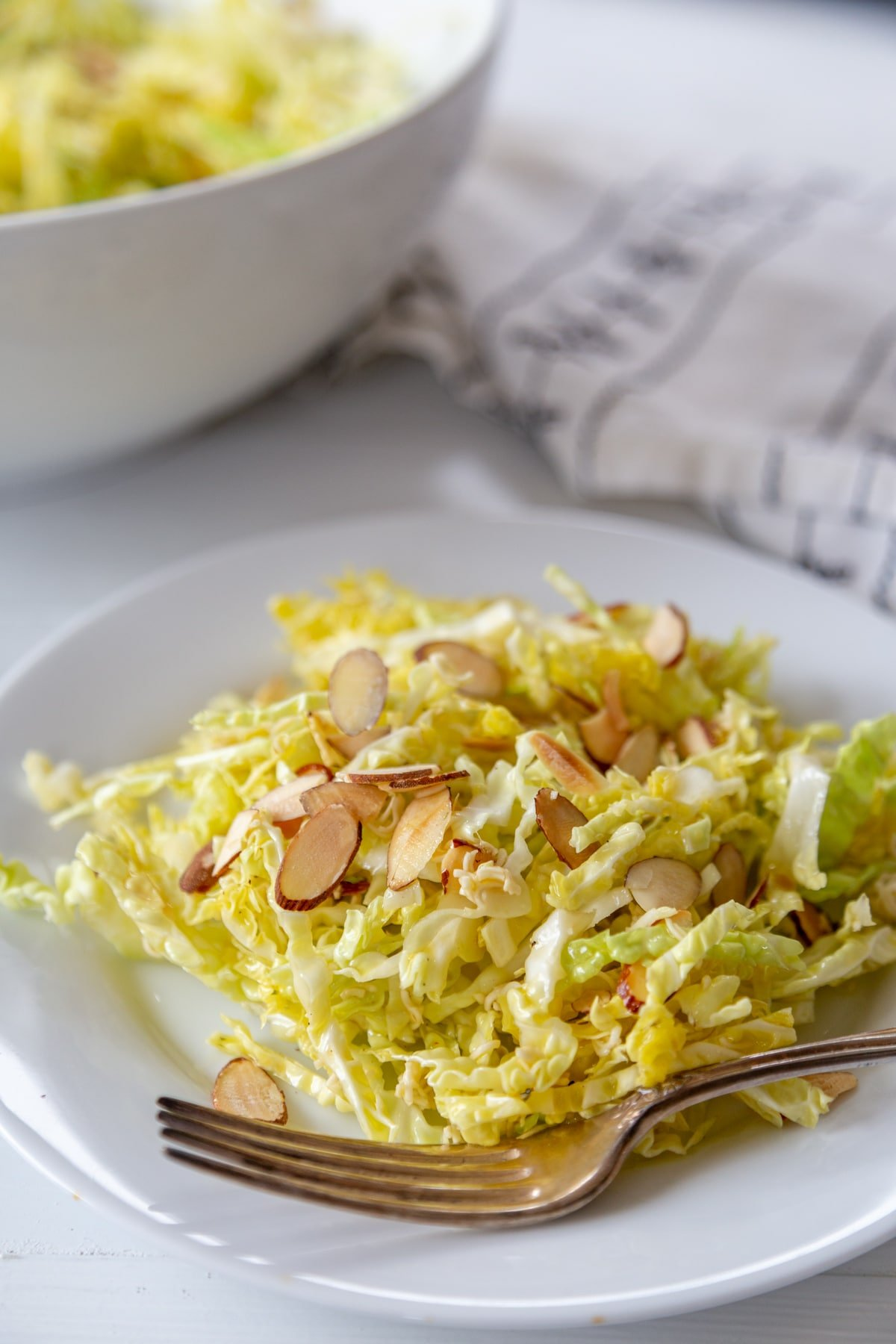Shredded cabbage salad with slivered almonds on a white plate with a silver fork on the side of the plate and a white bowl of the salad in the background.