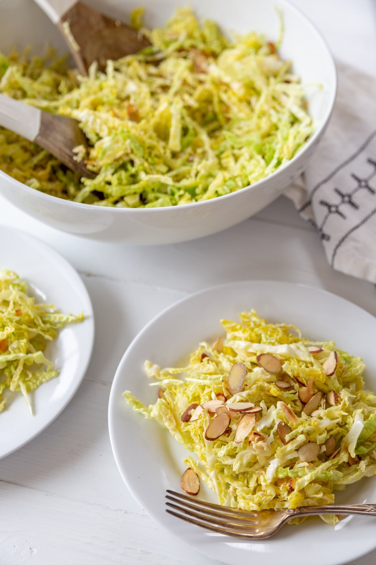 A white plate with shredded cabbage and almond salad with a silver fork on the edge of the plate, part of a white plate with salad on the left, and a white bowl of the salad with white and wood salad serving pieces in the bowl.
