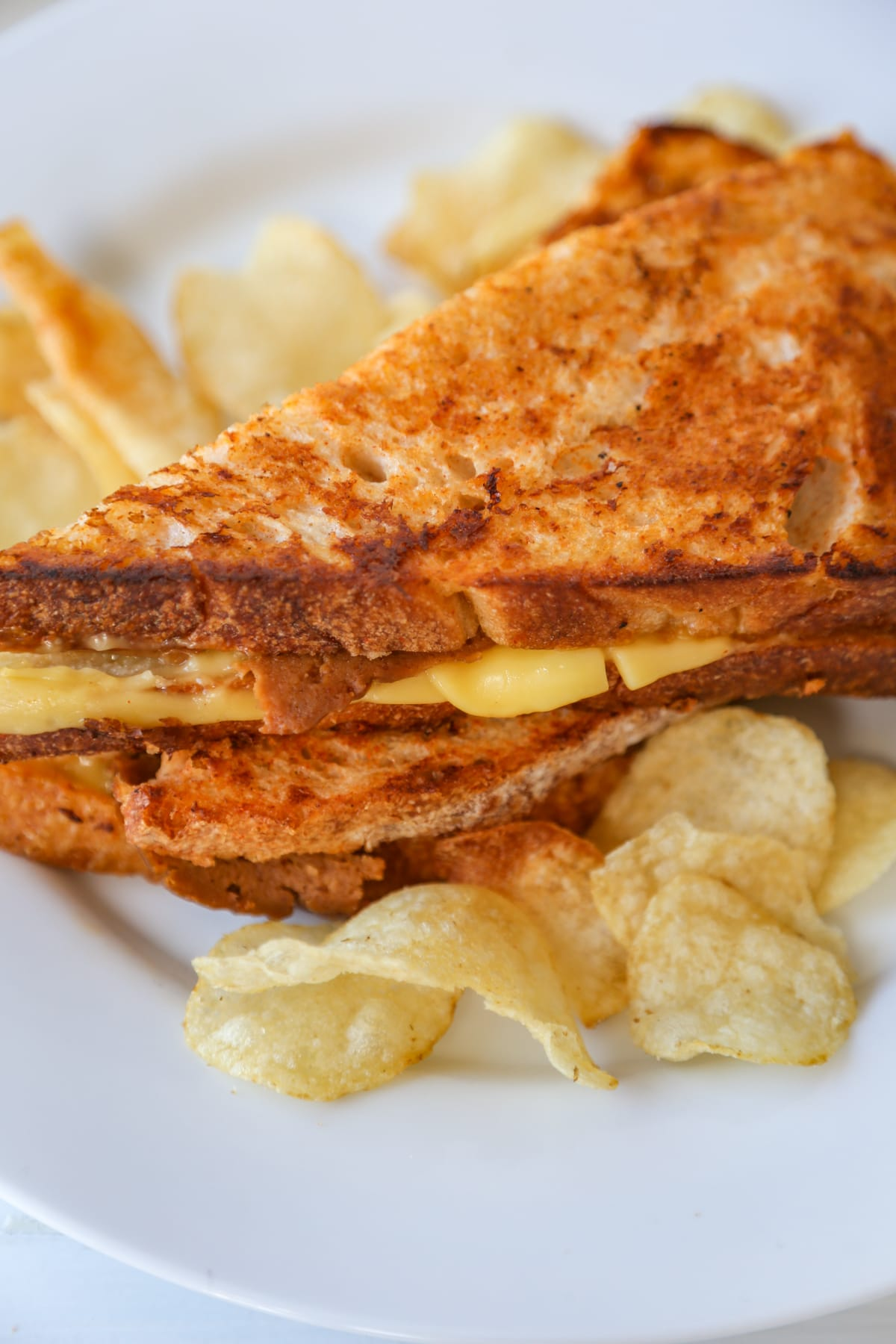 A grilled monte cristo sandwich cut in half in triangles and stacked, with potato chips on a white plate.