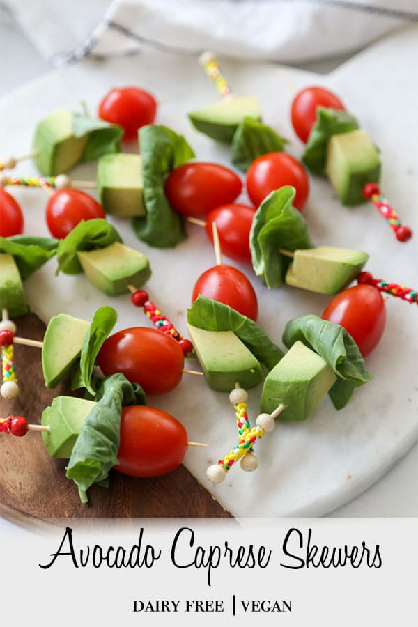 A PInterest pin for avocado caprese skewers with a picture of the skewers on a wood and marble board.
