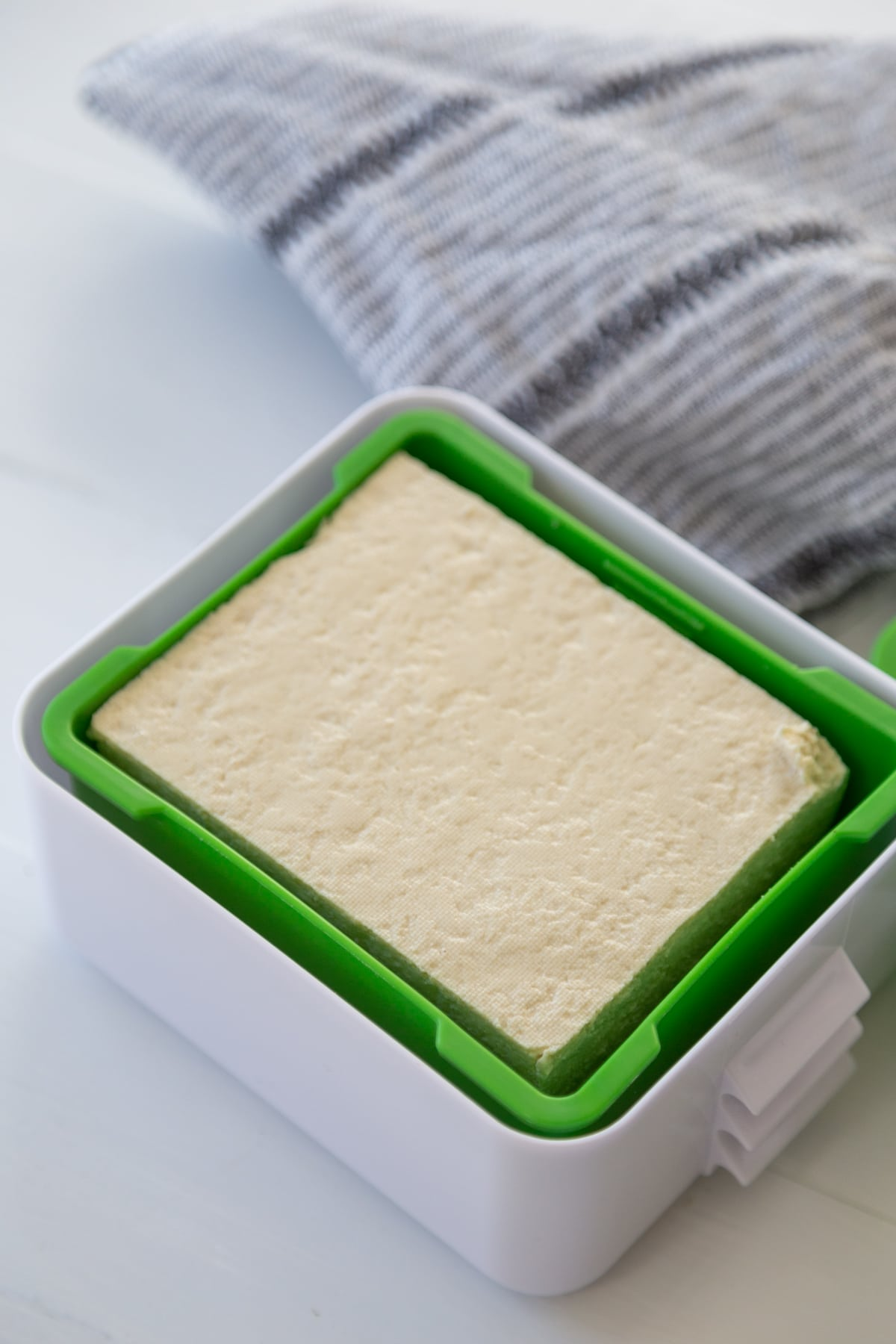 A block of tofu in a green and white tofu press.