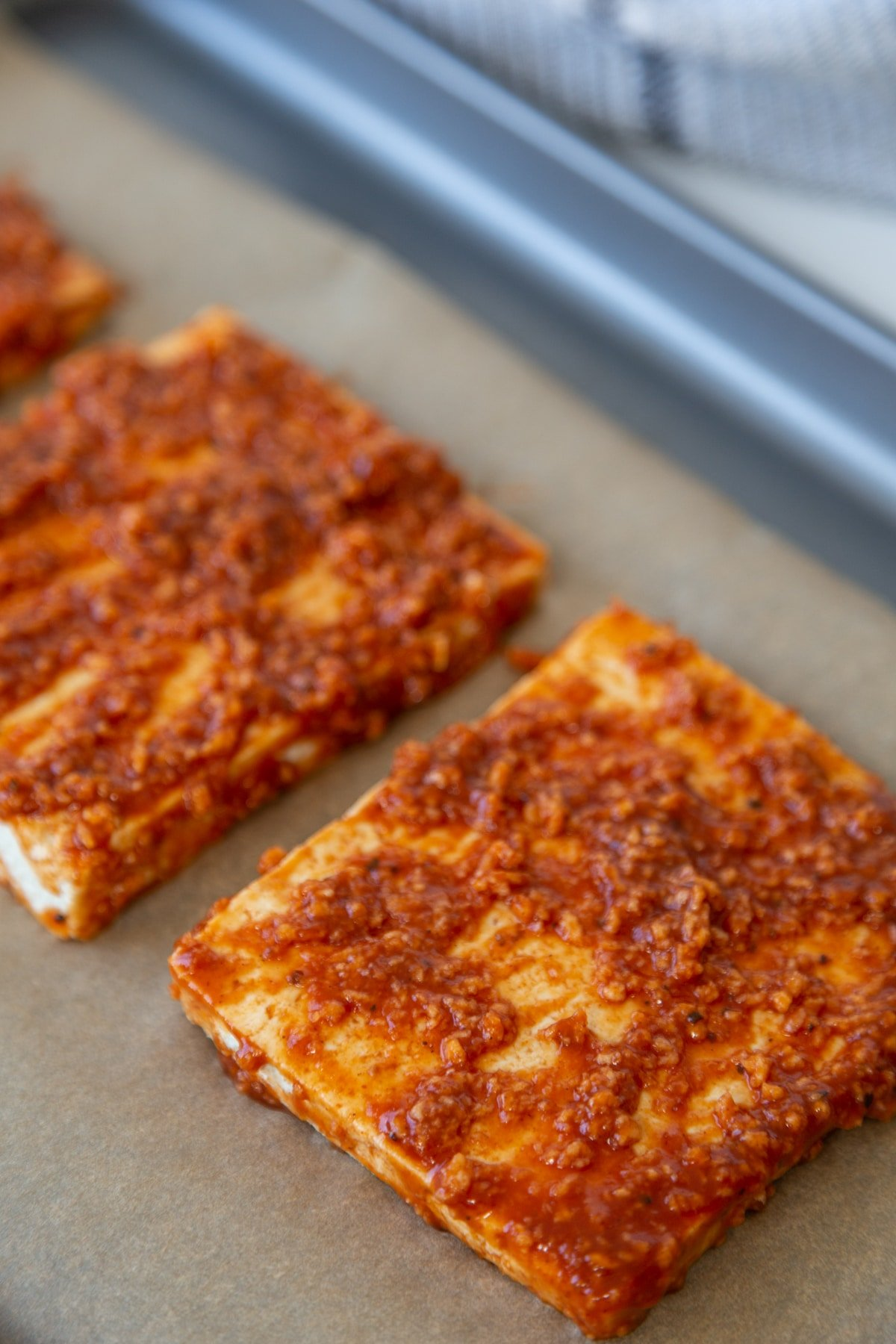 3 barbecue tofu steaks on a baking sheet lined with parchment paper.
