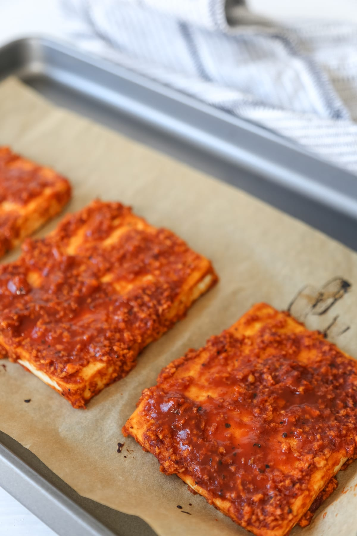 2 square pieces of tofu with barbecue sauce on a baking sheet with parchment paper.