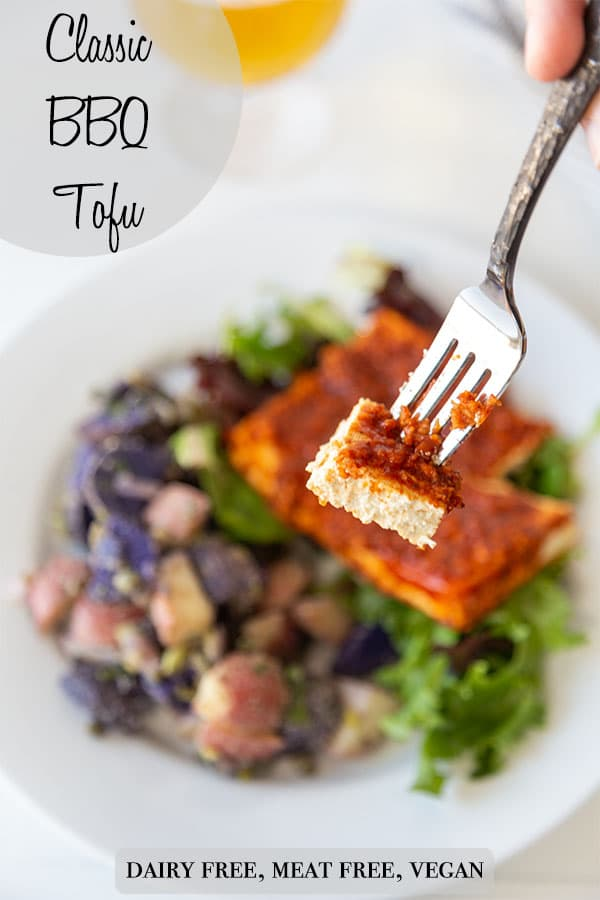 A Pinterest pin for bbq tofu with a picture of a silver fork with a slice of the tofu held above the plate with the tofu and potato salad.