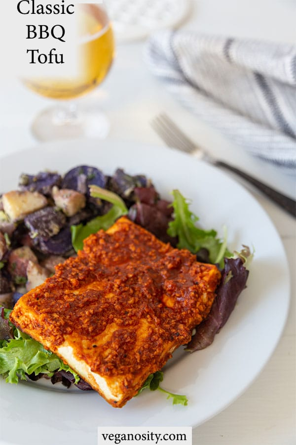 A Pinterest pin for crispy bbq tofu with a picture of the tofu and potato salad on a white plate.