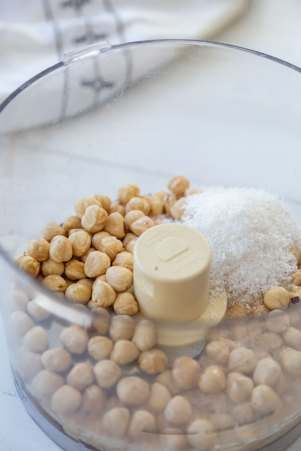 A food processor with hazelnuts and dried coconut.