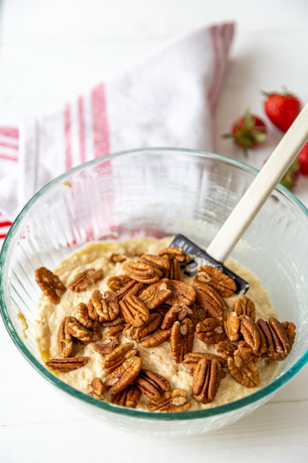 A glass mixing bowl with waffle batter and a spatula stirring toasted pecans into the batter.