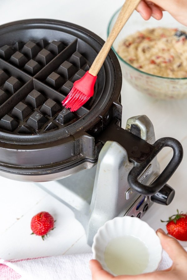 A red silicone pastry brush brushing oil on a waffle iron.