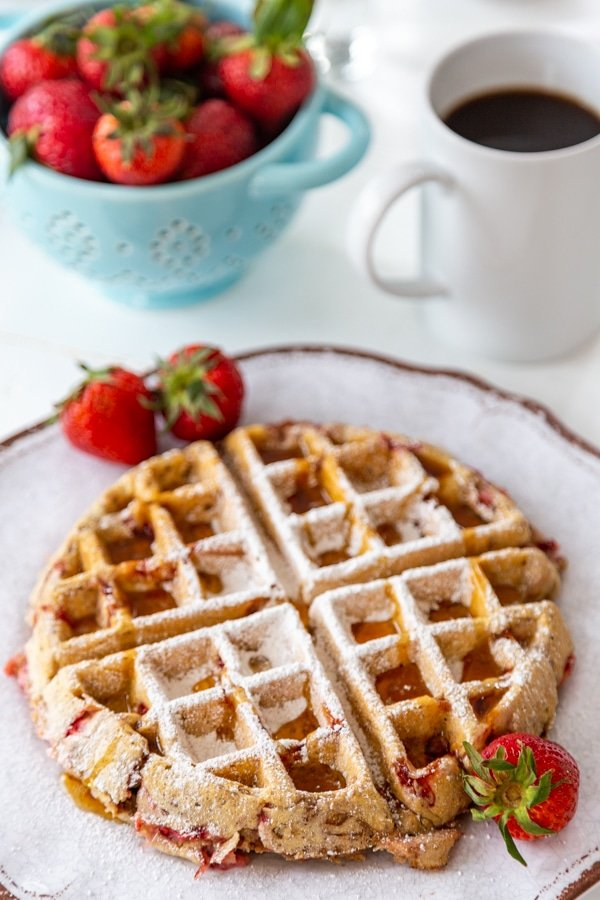 A strawberry pecan Belgian waffle on a white plate with strawberries on the side and powdered sugar sprinkled on top, and a blue bowl of strawberries and a cup of coffee in the background.