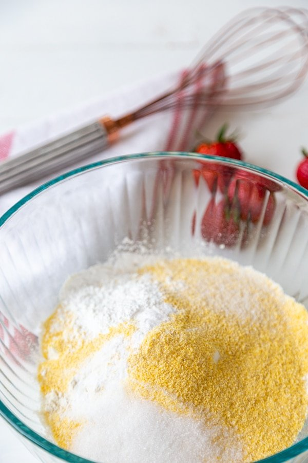 A glass mixing bowl with flour, cornmeal, and sugar.