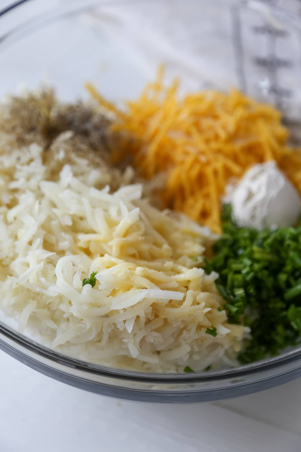 A glass bowl with shredded potato, shredded cheese, minced chives, and flour.