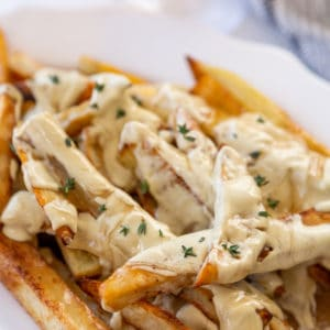 A white oval platter with fries that are covered in cheese sauce and gravy, and sprinkled with thyme leaves.