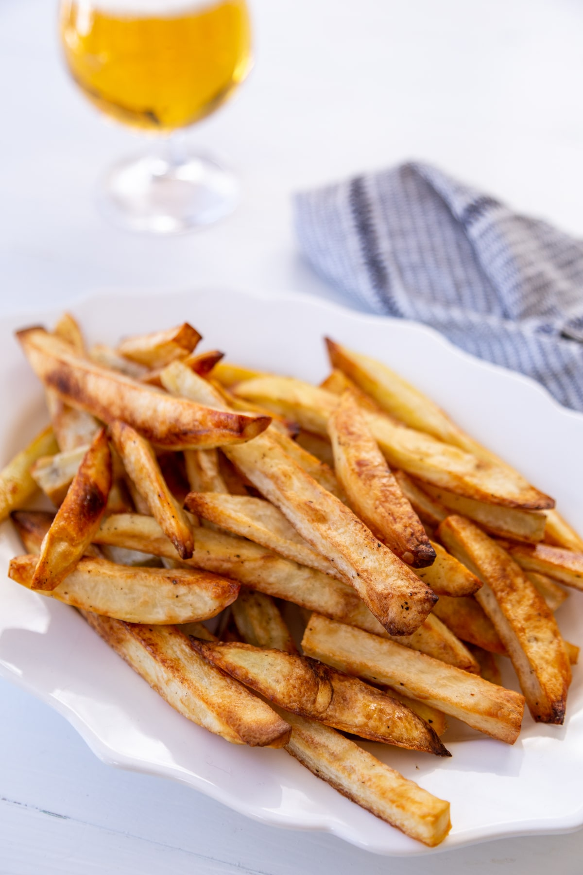 A white oval scalloped edge platter with a pile of fries and a glass of beer and a black and white towel next to the platter.