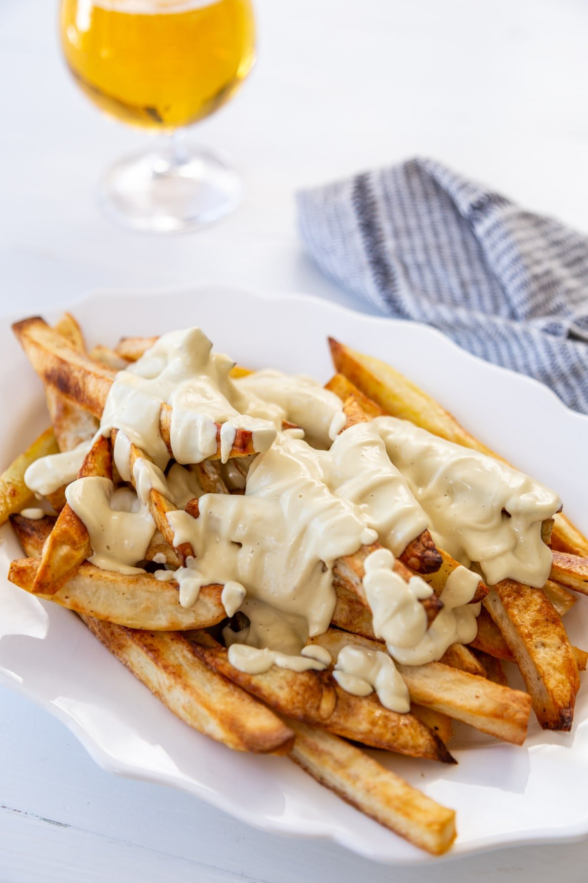 A platter of fried with cheese sauce and gravy next to a glass of beer and a black and white napkin.