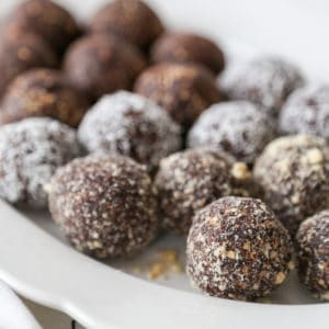 A white scalloped edge platter with chocolate breakfast balls, some covered in coconut.