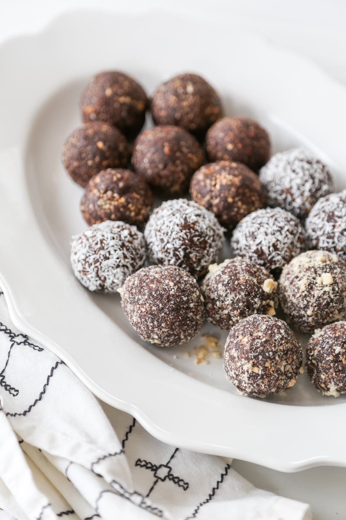 Vegan chocolate breakfast balls, some rolled in shredded coconut, on a white scalloped edged platter.