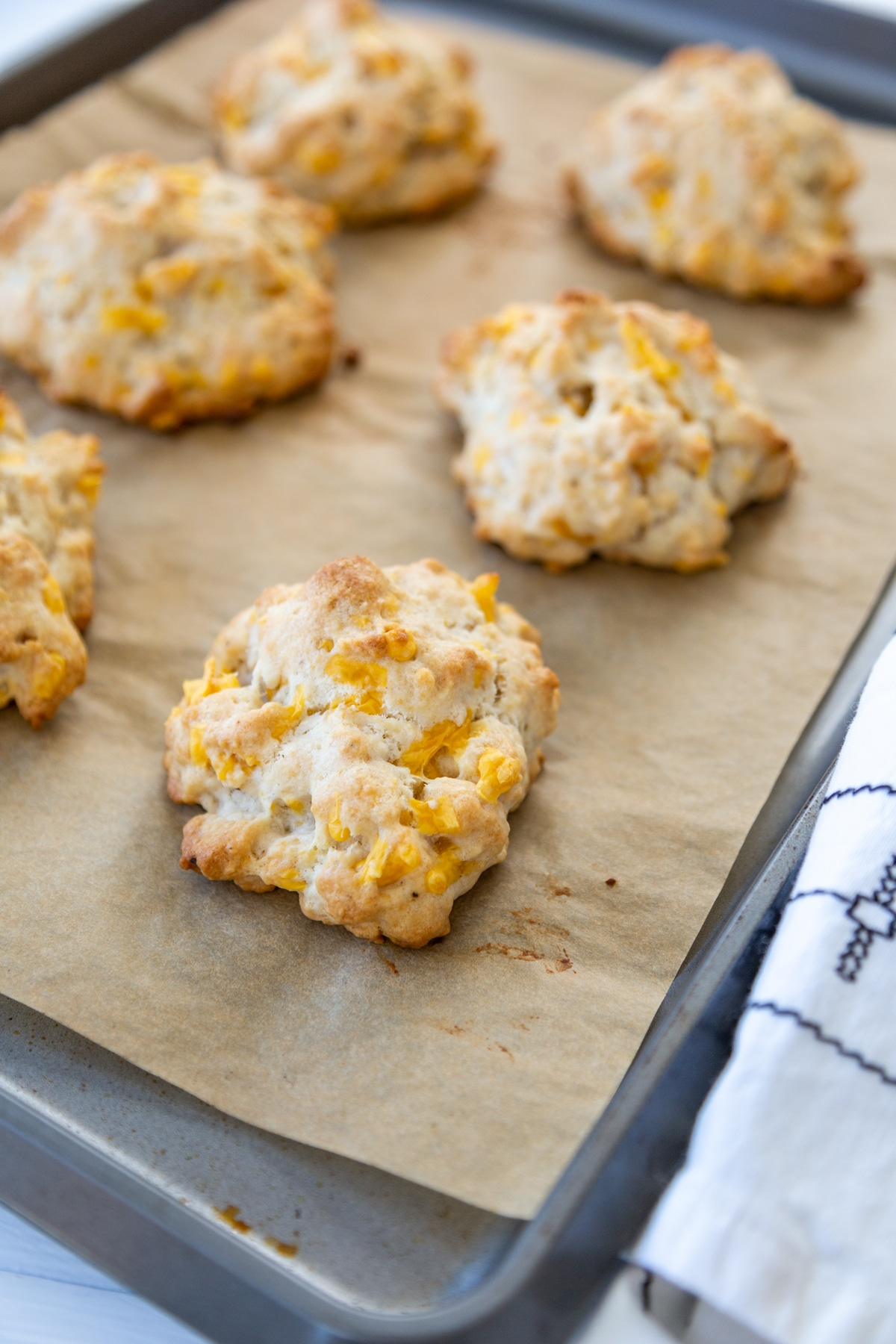 6 cheddar biscuits on a parchment lined baking sheet.