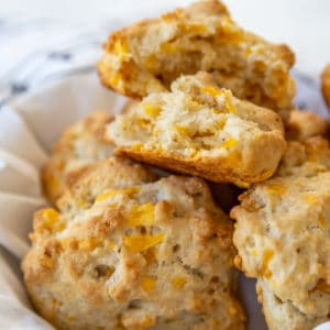 A basket of cheddar drop biscuits with the top biscuit torn in half to show the melted cheese and the texture.