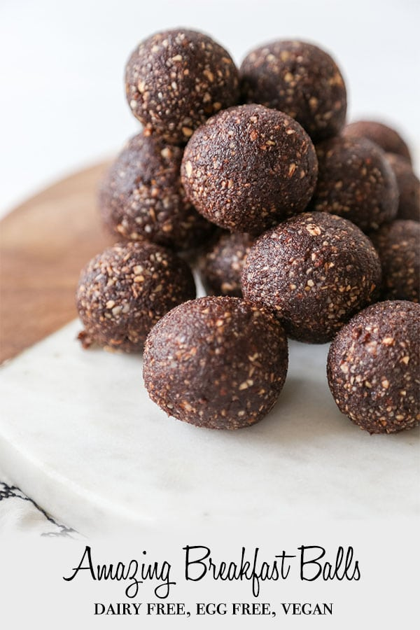 A Pinterest pin for chocolate breakfast balls with a stack of the balls on a round marble and wood board.