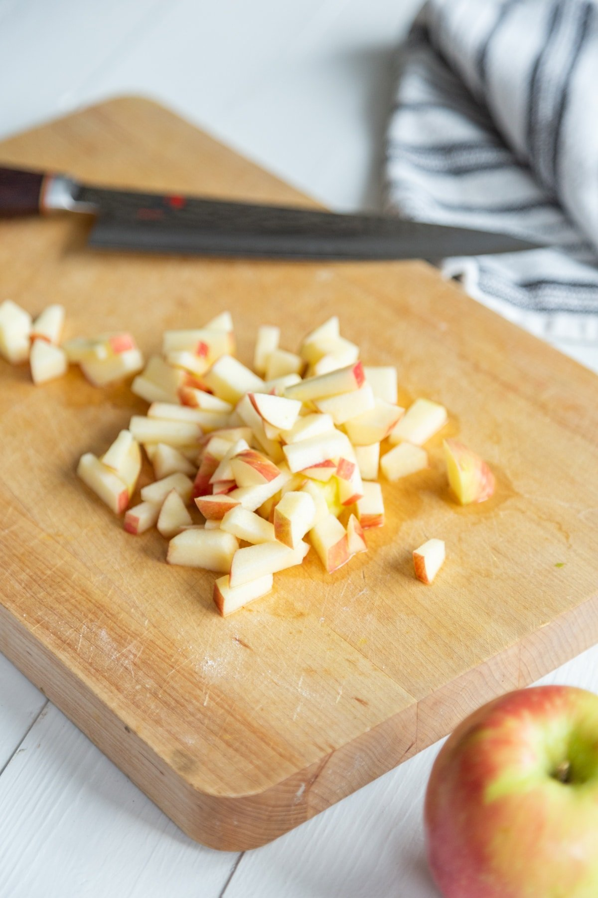 A wood cutting board with a knife and chopped apples and a whole red apple and a towel next to the board.