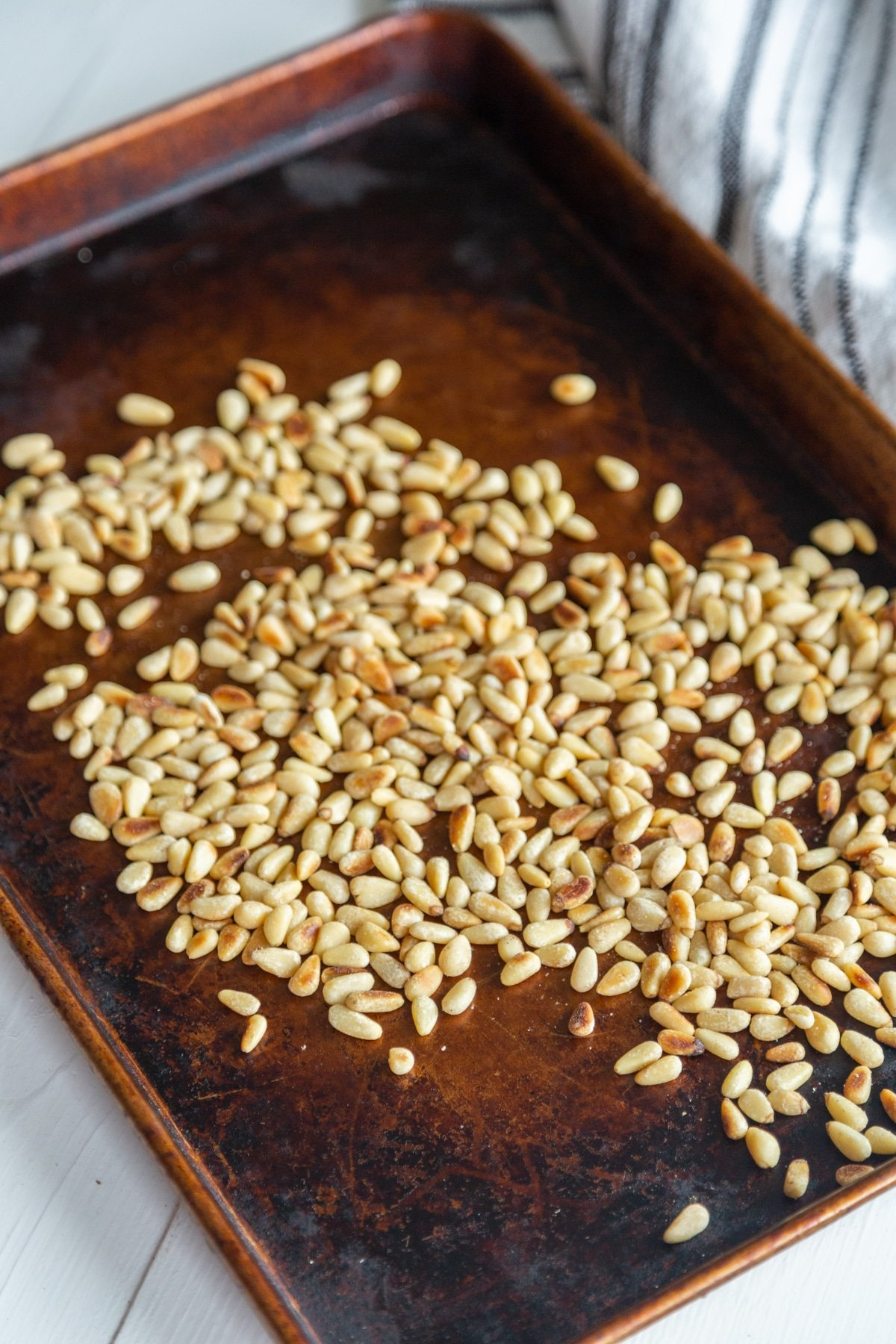 Toasted Pine Nuts on a rimmed baking sheet.